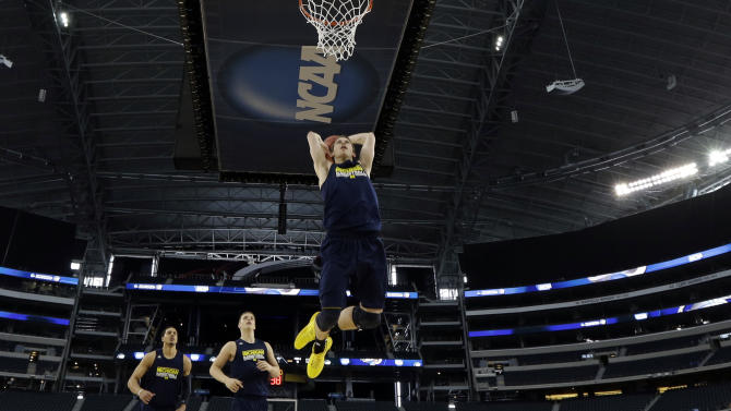 CORRECTS CITY TO ARLINGTON, TEXAS; NOT DALLAS - Michigan's Nik Stauskas dunks during practice for a regional semifinal game in the NCAA college basketball tournament, Thursday, March 28, 2013, in Arlington, Texas. Michigan faces Kansas on Friday. (AP Photo/David J. Phillip)