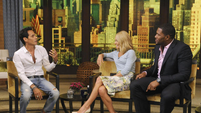 """This image released by Disney-ABC Domestic Television shows Mark Anthony, left, with co-hosts Kelly Ripa, center, and Michael Strahan on """"Live with Kelly and Michael,"""" Thursday, July 18, 2013, in New York. Marc Anthony touted his roots on """"Live with Kelly and Michael"""" on Thursday after some people criticized his selection to sing """"God Bless America"""" at this week's major league baseball All-Star Game, held in New York. The Grammy-winning salsa star said that he heard people were questioning why a foreign-born person was singing the patriotic song. Anthony said he was born in New York and added: """"You can't get more New York than me."""" (AP Photo/Disney-ABC Domestic Television, Jeff Neira)"""