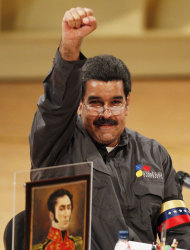 Venezuela's acting President Nicolas Maduro gestures to people at the opening of the Ninth International Book Fair of Venezuela (Filven) which pays tribute to late President Hugo Chavez at the Teresa Carreno theater in Caracas, Venezuela, Wednesday, March 13, 2013. The picture at bottom left is of independence hero Simon Bolivar. Maduro announced on March 5 that Chavez had died, after a nearly two-year bout with cancer. He was 58. (AP Photo/Ariana Cubillos)