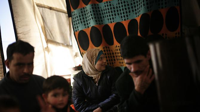 Syrian refugee family is seen at their tent in a refugee camp near Azaz, north of Aleppo province, Syria, Sunday, Feb. 17, 2013. (AP Photo / Manu Brabo)