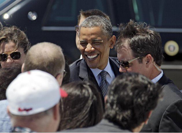 President Barack Obama greets supporters after arriving at Cleveland Hopkins International airport in Cleveland, Thursday, June 14, 2012, before attending a campaign event in the city. (AP Photo/Mark