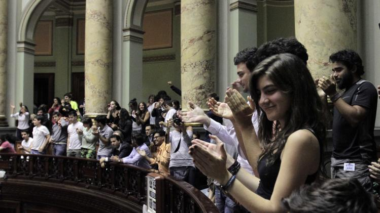 People celebrates after Uruguay's Senate approved a government-sponsored bill establishing state regulation of the cultivation, distribution and consumption of marijuana during a session in Montevideo