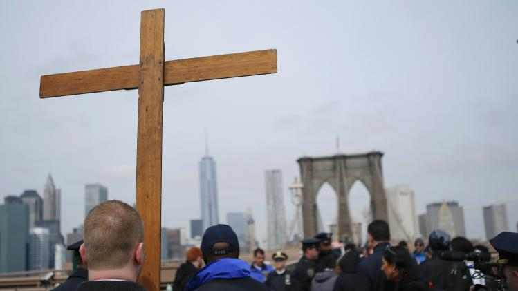 "People participate in the 19th annual ""Way of the Cross Over the Brooklyn Bridge Ceremony"" in New York City"