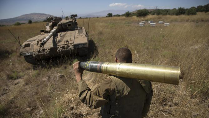 An Israeli soldier carries a tank shell near Alonei Habashan on the Israeli occupied Golan Heights