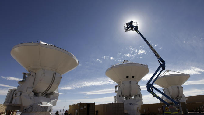 In this Sept. 26, 2012 photo, people work on antennas at the European assembly area at one of the worlds largest astronomy projects, the Atacama Large Millimeter/submillimeter Array (ALMA) in the Atacama desert in northern Chile. Linked as a single giant telescope, the radio antennas pick up wavelengths of light longer than anything visible to the human eye and colder than infrared telescopes, which are good at capturing images of distant suns but miss planets and clouds of gases from which stars are formed.  (AP Photo/Jorge Saenz)