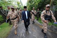This file photo shows Murad Ebrahim (C), chairman of the Moro Islamic Liberation Front (MILF), being escorted by his troops at Camp Darapan, Sultan Kudarat province, on the southern Philippine island of Mindanao, in 2011. Ebrahim is due to arrive in Manila on Sunday for a historic visit aimed at ending one of Asia's longest and deadliest insurgencies
