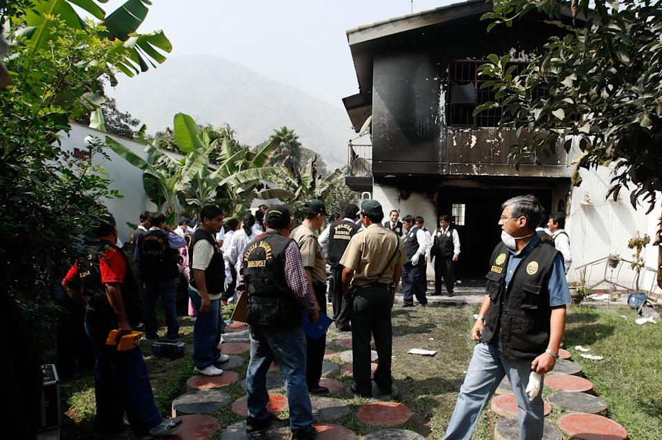 Police officers stand outside the site of a pre-dawn blaze, at the Sacred Heart of Jesus clinic in Chosica, Peru, Saturday, May 5, 2012. A fire swept through the rehabilitation center for addicts near the Peruvian capital of Lima and officials say at least 14 people are dead. (AP Photo/Karel Navarro)