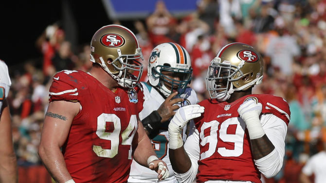 San Francisco 49ers outside linebacker Aldon Smith (99) is greeted by teammate Justin Smith (94) after sacking Miami Dolphins quarterback Ryan Tannehill, bottom, during the first quarter of an NFL football game in San Francisco, Sunday, Dec. 9, 2012. (AP Photo/Marcio Jose Sanchez)