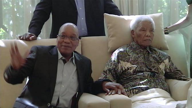 """FILE : In this image taken from video, South African President Jacob Zuma, left, sits with the ailing anti-apartheid icon Nelson Madela is filmed Monday April 29, 2013, more than three weeks after being released from hospital. Mandela was treated in hospital for a recurring lung infection.  South African President Jacob Zuma visited the former leader on April 29, but Mandela does not appear to speak during the televised portion of the visit, as he sits in an armchair, his head propped up by a pillow and with his cheeks showing what appear to be marks from a recently removed oxygen mask, although Zuma said he found Nelson Mandela """"in good shape and in good spirits"""".  After the encounter at Mandela's home, Zuma cheerily said the 94-year-old was up and about, in good spirits and doing well.  (AP Photo/SABC TV) SOUTH AFRICA OUT"""