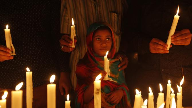 A girl holds candle for the victims of the attack by Taliban gunmen on the Army Public School in Peshawar, during a prayer service organized by the members of the Sikh and Hindu communities at Gurdwara Guru Nanak Shah Karachi