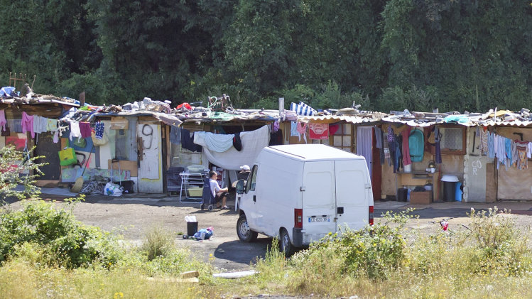 FILE - This Friday Aug. 10, 2012, file photo shows a Roma encampment set up near a highway in Clamart, west of Paris. A leading human rights group is calling on France to end its policy of forced evictions of Roma, saying they're being expelled from camps in record numbers and forced to wander between makeshift homes. France's top security official on Wednesday, Sept. 25, 2013, defended the policy and went further, saying France has no obligation to welcome people who cannot support themselves. (AP Photo/Michel Euler, File)