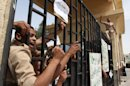 "Egyptian border policemen shout at the closed Rafah border crossing between Egypt and the Gaza strip to protest the abduction of their colleagues last Thursday, in Rafah, Sinai, Egypt, Sunday, May 19, 2013. Rafah, the main crossing point into the Gaza Strip, was closed by policemen Friday, barring people from going in or out of the Palestinian territory. Scores of protesting Egyptian police have also shut down the Awja commercial border crossing with Israel Sunday. Arabic reads, ""This is a strike and not a protest. Where is Morsi, Kandil and our brothers?"" (AP Photo/Roger Anis, El Shorouk Newspaper) EGYPT OUT"