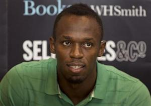 """Jamaican athlete Usain Bolt poses for photographers as he signs copies of his autobiography, """"Faster than Lightning,"""" at Selfridges in central London"""