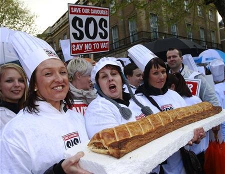 Bakers and their supporters hold a giant sausage roll as they protest opposite Downing Street in central London