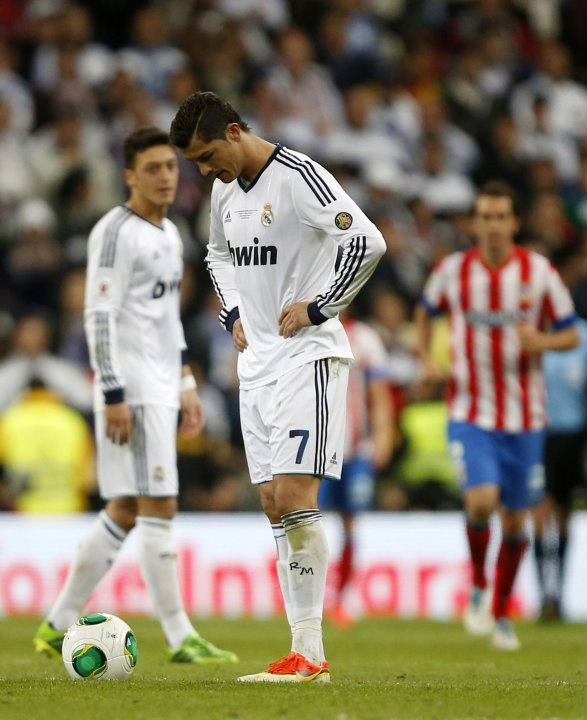 Real Madrid's Cristiano Ronaldo and Mesut Ozil react after Atletico de Madrid's Miranda scored a goal during their Spanish King's Cup final soccer match at Santiago Bernabeu stadium in Madrid