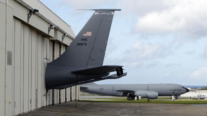 In this Aug. 14, 2012 photo, the tail of a U.S. Air Force KC-135 Stratotanker protrudes from a hanger as ground crew members walk past another KC-135, at Kadena Air Base on Japan's southwestern island of Okinawa. The most recent of the KC-135 refueling tankers currently in service started flying in 1964. For decades, the U.S. Air Force has grown accustomed to such superlatives as unrivaled and unbeatable. Now some of its key aircraft are being described with terms like decrepit.   (AP Photo/Greg Baker)