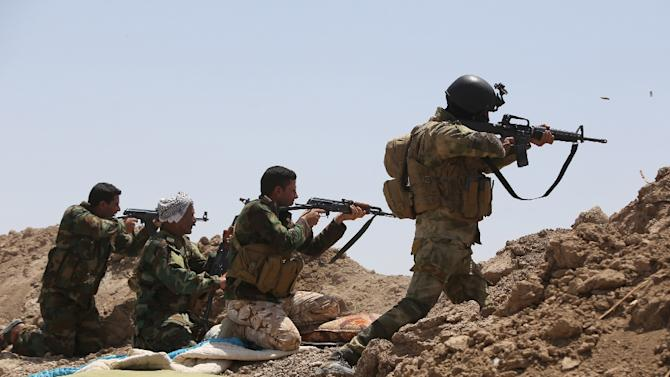 Iraqi soldiers and Shiite fighters from the popular committees fire towards Islamic State (IS) positions in the Garma district of Anbar province on May 19, 2015