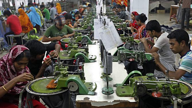 """In this Saturday, Dec. 8, 2012, photo, Bangladeshi garment workers manufacture clothing in a factory on the outskirts of  Dhaka, Bangladesh. About a year before a November fire at a clothing factory in Bangladesh killed 112 people, executives from Wal-Mart, Gap and other big clothing companies met nearby in the country's capital to discuss a legally binding contract that would govern safety inspections. But after a spokeswoman for Wal-Mart, the world's largest retailer, got up and said the proposal wasn't """"financially feasible,"""" the effort quickly lost momentum. (AP Photo/A.M. Ahad)"""