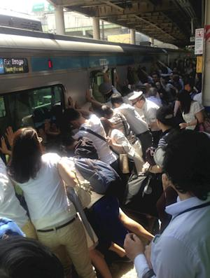 Pushy train passengers free woman stuck in gap