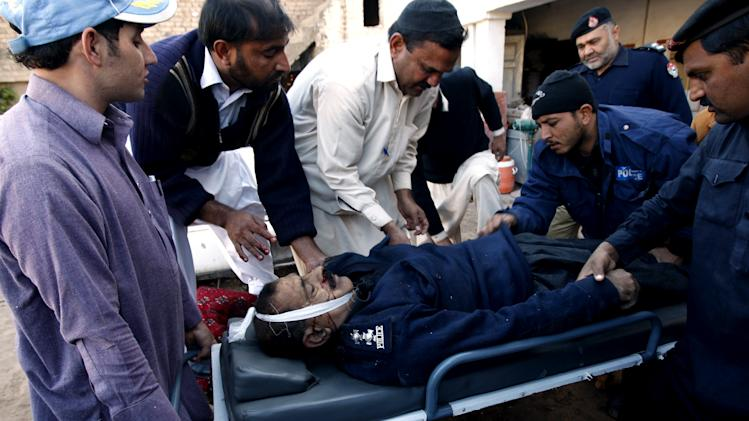 Rescue workers carry the body of a police officer killed in a blast on Monday, Dec. 3, 2012 in Peshawar, Pakistan. A bomb ripped through a police van as it was patrolling in northwestern Pakistan on Monday, killing several officers and wounding others, police said. (AP Photo/Mohammad Sajjad)