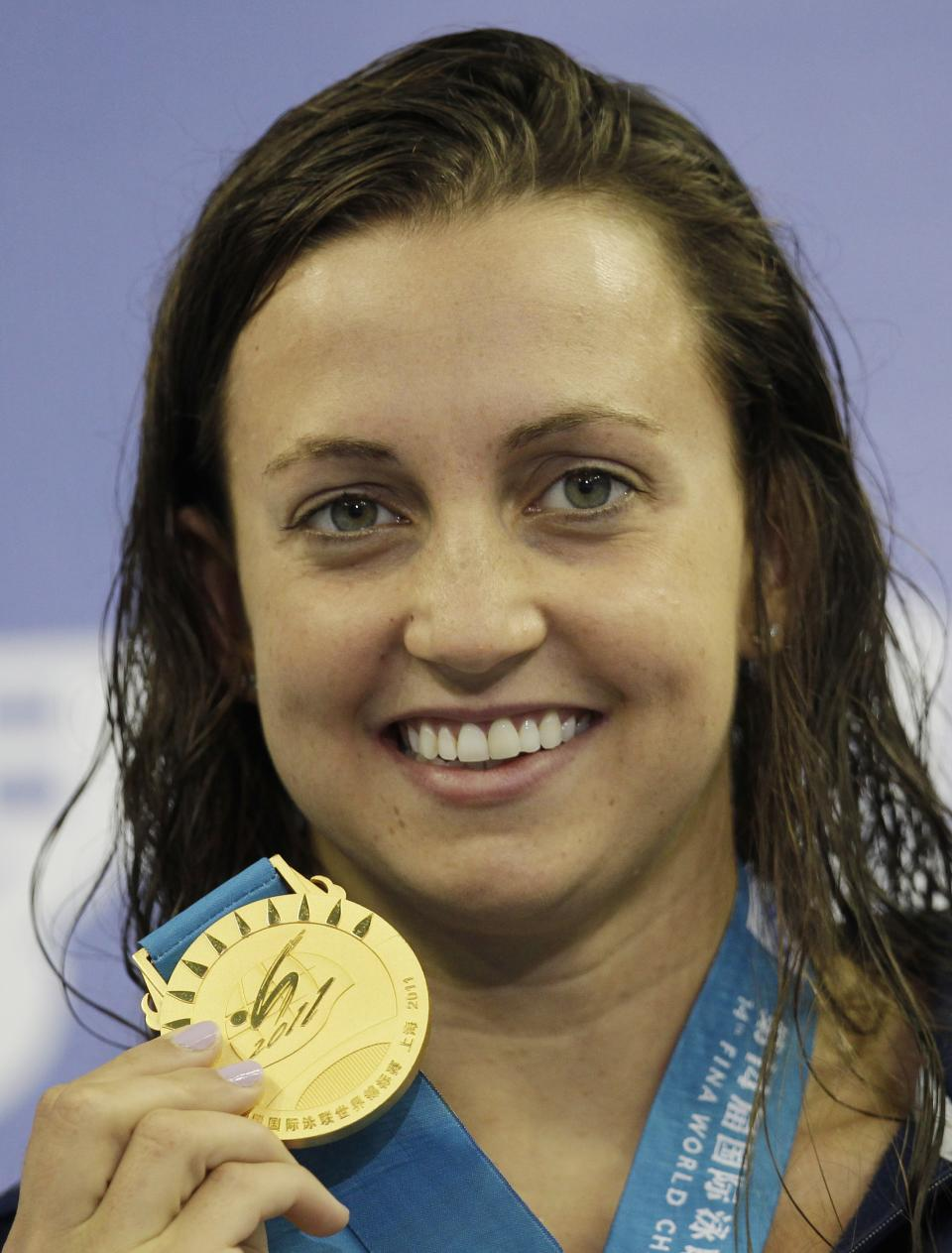 Rebecca Soni of the U.S. holds up her gold medal she won in the women's 100m Breaststoke event at the FINA Swimming World Championships in Shanghai, China, Tuesday, July 26, 2011. (AP Photo/Michael Sohn)