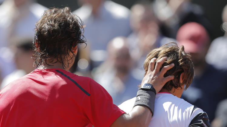 Rafael Nadal of Spain pats compatriot David Ferrer on the head after winning his semi final match at the French Open tennis tournament in Roland Garros stadium in Paris, Friday June 8, 2012. Nadal won in three sets 6-2, 6-2, 6-1. (AP Photo/Bernat Armangue)