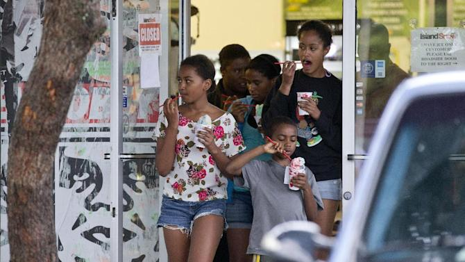 Sasha Obama, left, and Malia Obama back right, eat their shave ice as they exits Island Snow with family members and friends ahead of their father President Barack Obama, Thursday, Jan. 3, 2013, in Kailua, Hawaii. President Obama and the first family are in Hawaii for a holiday vacation. (AP Photo/Carolyn Kaster)