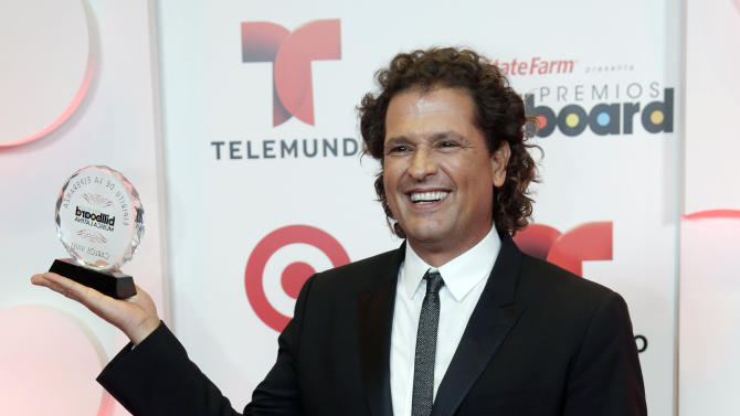 """In this April 24, 2014 file photo, singer Carlos Vives holds the Billboard Spirit of Hope Award during the Latin Billboard Awards, in Coral Gables, Fla. Vives, 52, said bringing the families to the World Cup would serve as additional """"motivation for the players."""" Colombia, which will play Ivory Coast on Thursday, June 19, 2014, is taking part in its first World Cup since 1998.(AP Photo/Wilfredo Lee, file)"""