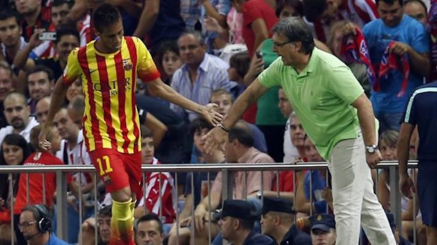 "Barcelona's Neymar (L) is congratulated by his coach Gerardo ""Tata"" Martino after scoring a goal against Atletico Madrid during their Spanish SuperCup first leg soccer match at Vicente Calderon stadium in Madrid August 21, 2013. REUTERS"