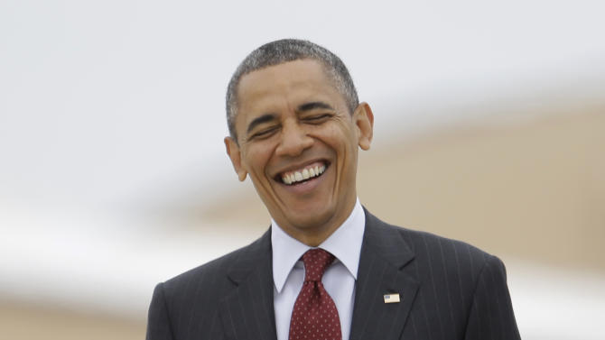 President Barack Obama laughs as he walks to board Air Force One, Sunday, May 5, 2013, in Andrews Air Force Base, Md., en route to speak at the Ohio State University spring commencement, in Columbus, Ohio. (AP Photo/Carolyn Kaster)