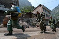 Chinese soldiers responsible for disinfecting the area march past a damaged building in Yunnan Province