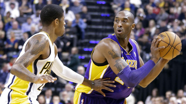 Los Angeles Lakers guard Kobe Bryant, right, looks to pass around Indiana Pacers forward Paul George in the first half of an NBA basketball game in Indianapolis, Friday, March 15, 2013.  (AP Photo/Michael Conroy)