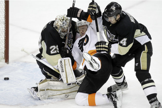 Philadelphia Flyers' Scott Hartnell (19) collides with Pittsburgh Penguins goalie Marc-Andre Fleury (29) and defenseman Zbynek Michalek (4) as the puck slides across the goal line for a first-period g