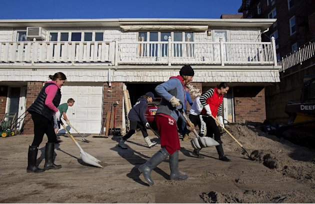 Neighbors volunteering to help another neighbor in need move deep sand from the house on Beach 121 Street in the Rockaway Park neighborhood of the borough of Queens, New York, Sunday, Nov. 11, 2012, i