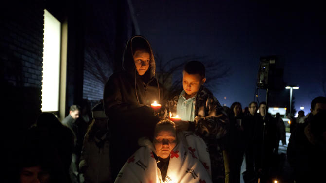 Sharon Bertrand, center, listens with her daughter Daysha, 13, left, and son Juan, all of Waterbury, Conn., to a memorial service over a loudspeaker outside Newtown High School for the victims of the Sandy Hook Elementary School shooting, Sunday, Dec. 16, 2012, in Newtown, Conn. (AP Photo/David Goldman)