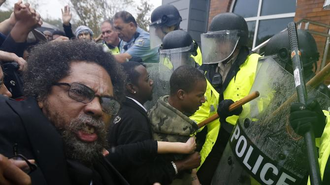Activist Cornel West is knocked over during a scuffle with police during a protest at the Ferguson Police Department in Ferguson