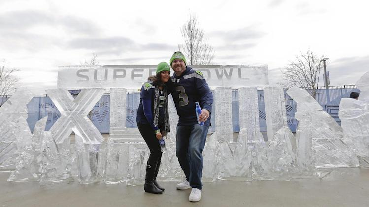 Seattle Seahawks fans Aaron Hulet, right, and Erica Hulet, pose for a picture in front of an ice sculpture before the NFL Super Bowl XLVIII football game between the Seattle Seahawks and the Denver Broncos Sunday, Feb. 2, 2014, in East Rutherford, N.J. (AP Photo/Matt York)