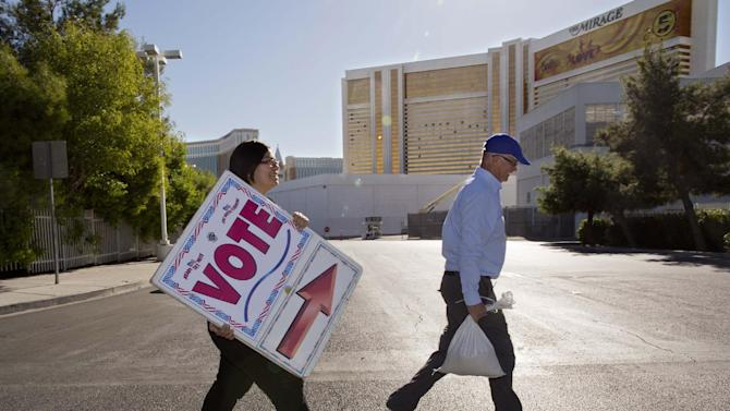 In this Oct. 20, 2012, photo, election workers Elena Soto, left, and Dave Carlson post early voting signs for a polling place along Frank Sinatra Blvd. behind The Mirage Hotel-Casino in Las Vegas. The nation's complexion is rapidly changing. A more racially and ethnically diverse population is rising so that, perhaps within three decades, whites will no longer be the majority. That means shifts in political power, the risk of intensified racial tensions and also the opportunity to forge a multiracial society unlike anything in America's past. (AP Photo/Julie Jacobson)