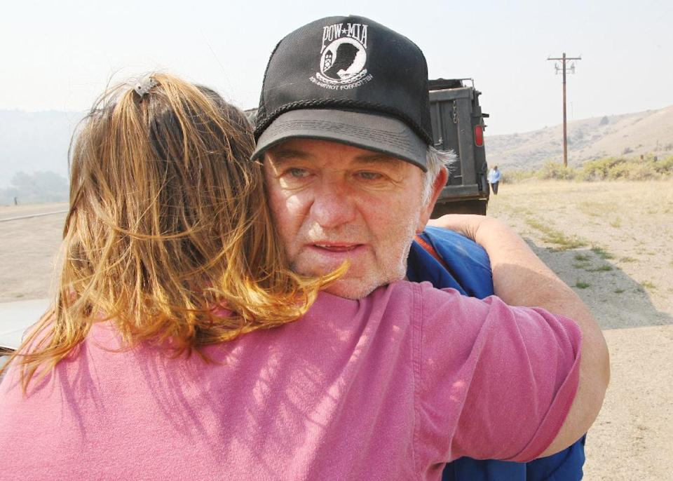 Janice Jansky hugs Joe Adams after he reported that her home was still standing in the Toll Mountain area of the 19-mile fire buring 10 miles southeast of Butte Wednesday morning Aug. 29, 2012. (AP Photo/Walter Hinick, Montana Standard)