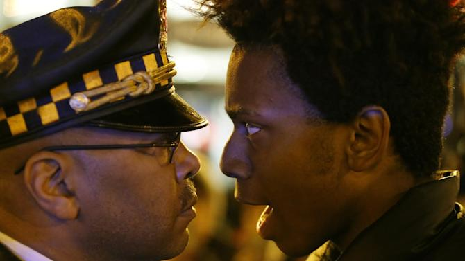 """Lamon Reccord, right, stares and yells at a Chicago police officer """"Shoot me 16 times"""" as he and others march through Chicago's Loop Wednesday, Nov. 25, 2015, one day after murder charges were brought against police officer Jason Van Dyke in the killing of 17-year-old Laquan McDonald. (AP Photo/Charles Rex Arbogast)"""
