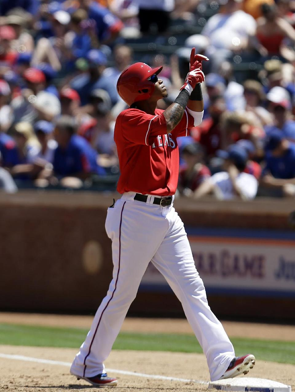 Texas Rangers' Engel Beltre points skyward after hitting for a single off a pitch from Cincinnati Reds' Mat Latos in the third inning of a baseball game Sunday, June 30, 2013, in Arlington, Texas. (AP Photo/Tony Gutierrez)