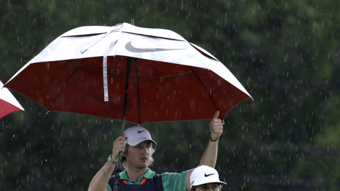 Thorbjorn Olesen, of Denmark, waits with his caddie during a weather delay during the first round of the U.S. Open golf tournament at Merion Golf Club, Thursday, June 13, 2013, in Ardmore, Pa. (AP Photo/Darron Cummings)