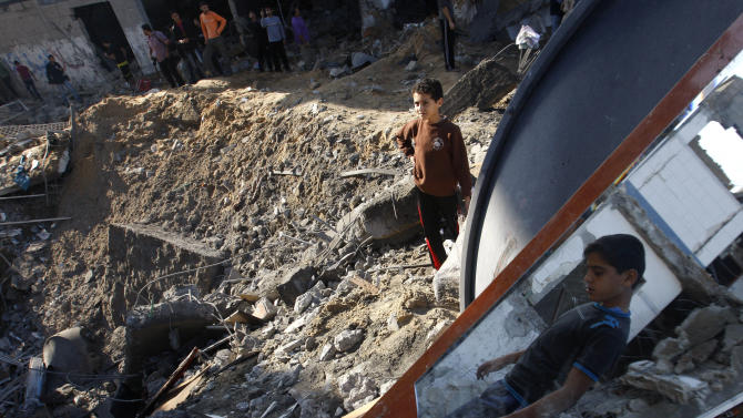 Palestinian children stand in the rubble left after an Israeli strike on a house in Gaza City, Tuesday, Nov. 20, 2012. Efforts to end a week-old convulsion of Israeli-Palestinian violence drew in the world's top diplomats on Tuesday, with President Barack Obama dispatching his secretary of state to the region on an emergency mission and the U.N. chief appealing from Cairo for an immediate cease-fire. (AP Photo/Hatem Moussa)