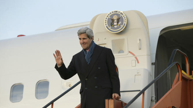 U.S. Secretary of State John Kerry waves upon his arrival in Brussels, Belgium, Tuesday, Dec. 3, 2013. Kerry traveled to Belgium to attend the annual meeting of NATO foreign ministers in Brussels. (AP Photo/Pablo Martinez Monsivais, Pool)