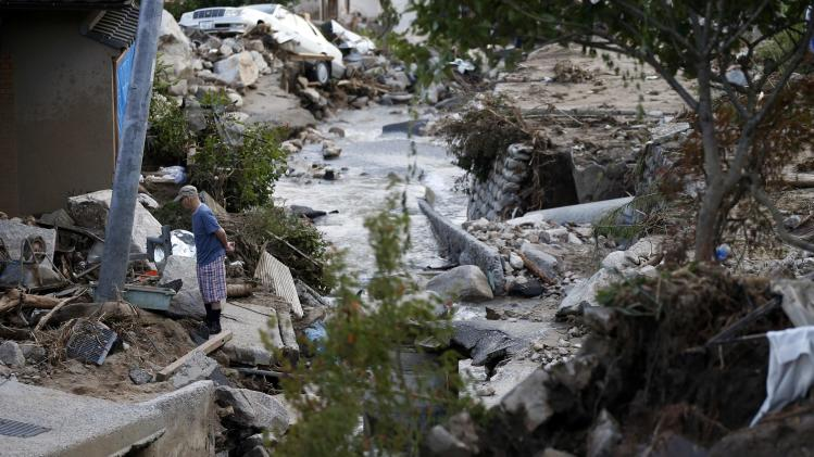 Local resident stands at a site where a landslide swept through a residential area at Asaminami ward in Hiroshima
