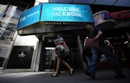 <p>People walk past a sign welcoming Facebook at the NASDAQ stock exchange on Times Square in New York, on May 18, 2012. Facebook raised $16 billion when it went public on May 18, giving it a nominal market value of a stunning $104 billion and raising hopes of a new dotcom boom on US markets.</p>