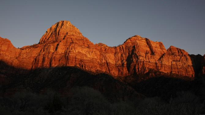 FILE - This Jan. 20, 2011 file photo shows shadows creeping up on sandstone cliffs glowing red as the sun sets on Zion National Park near Springdale, Utah. This is one of a number of scenic attractions, parks and other sites near enough to Las Vegas to add to itineraries as a day trip when visiting the gambling capital. (AP Photo/Julie Jacobson, file)