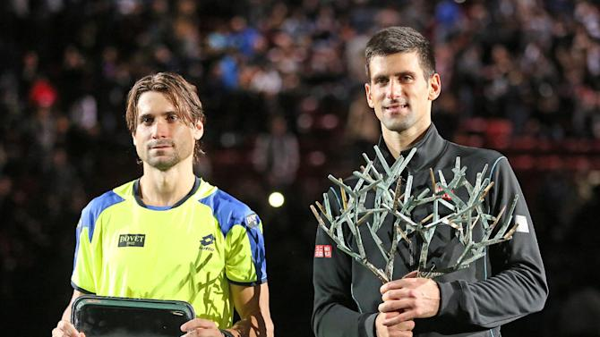 Serbia's Novak Djokovic, right, holds the trophy after winning the final of the Paris Masters tennis against Spain's David Ferrer, left, in the Paris Bercy stadium, Sunday Nov. 3, 2013.(AP Photo/Remy de la Mauviniere)