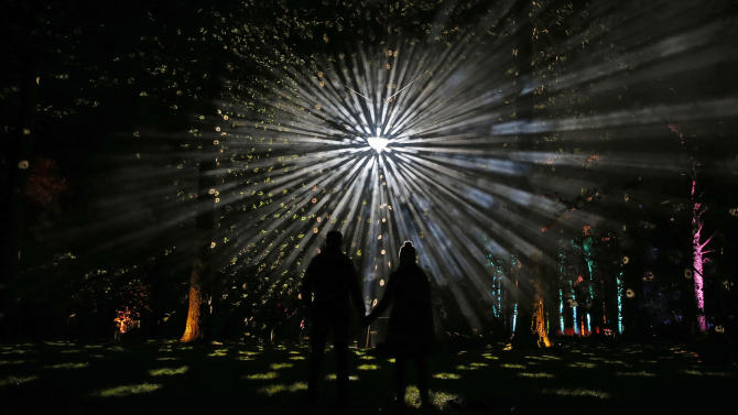Visitors pose for a photograph during the Enchanted Christmas event at the Forestry Commission's National Arboretum in Westonbirt