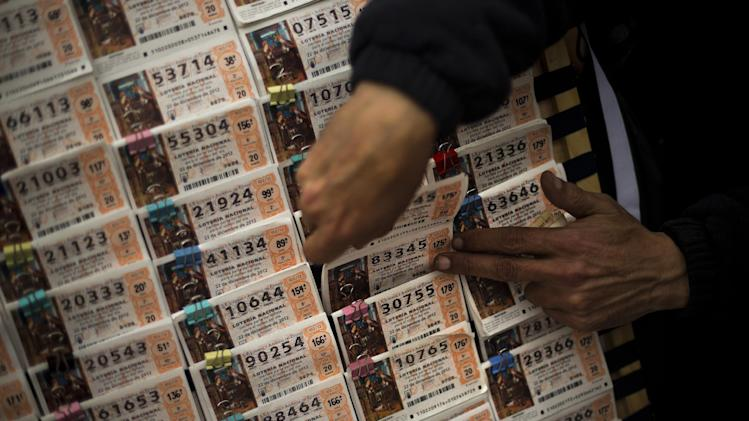 "A seller grabs tickets for the famed Christmas lottery, in Madrid, Friday, Dec. 21, 2012.   Known as ""El Gordo"" (The Fat One) and billed as the world's richest lottery, the drawing will hand out about 2.5 billion of euros (US dlrs 3.3 billion) on upcoming Saturday. The top prize is about 400,000 euros (US dlrs 530,000) but there are expected to be hundreds or thousands of tickets awarded for that amount. (AP Photo/Daniel Ochoa de Olza)"